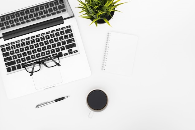 Un cahier vierge est au-dessus d'une table de bureau blanche avec un ordinateur portable, une tasse à café et des fournitures de bureau. vue de dessus avec fond