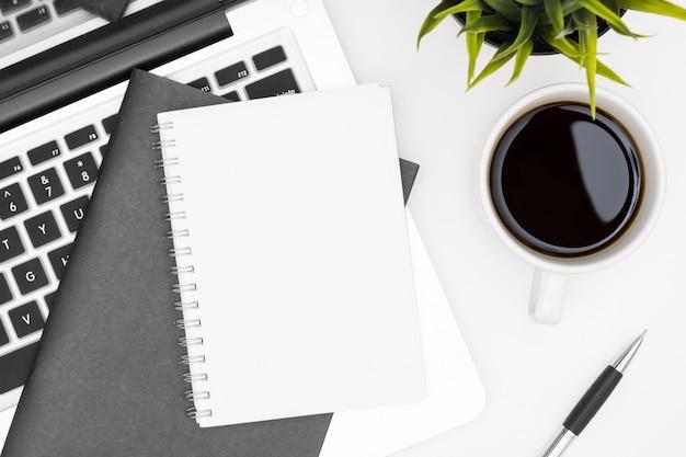 Un cahier vierge est au-dessus d'une table de bureau blanche avec un ordinateur portable, une tasse à café et des fournitures de bureau. vue de dessus