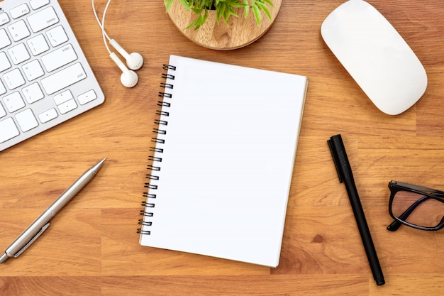 Cahier vierge est sur la table de bureau en bois avec fournitures. vue de dessus, plat poser.
