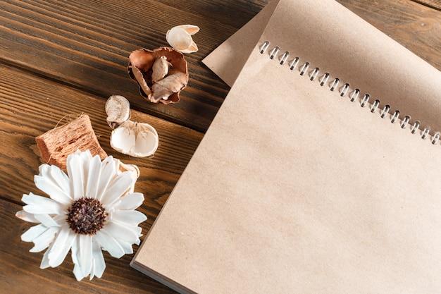 Cahier vierge avec fleur sur table en bois vintage