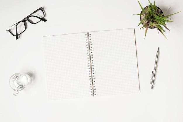 Un cahier vierge avec des lignes de quadrillage se trouve sur le bureau blanc.