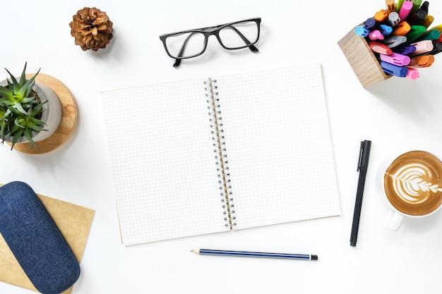 Un cahier vierge avec des lignes de quadrillage se trouve sur la table de bureau blanche avec fournitures.