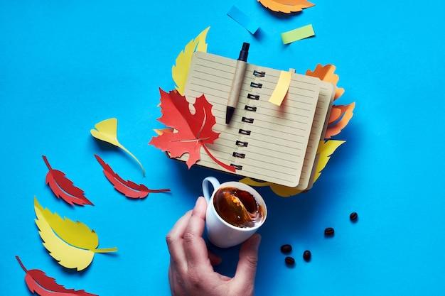 Cahier vierge ouvert avec des feuilles d'automne et de la main avec du café sur bleu