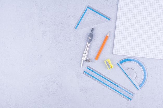 Cahier vierge avec règle et stylos autour