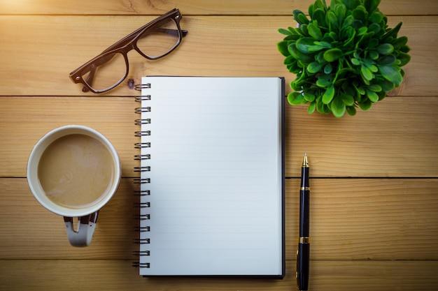 Cahier vierge avec stylo et lunettes à côté de la tasse de café sur la table en bois
