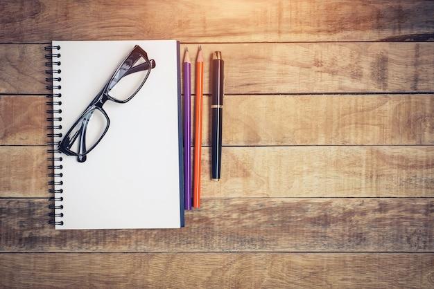 Cahier vierge avec stylo et lunettes sur table en bois