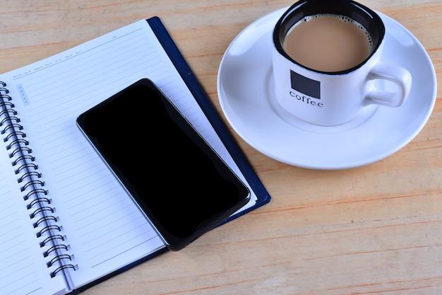 Cahier vierge, stylo plume, smartphone et tasse de café sur le bureau