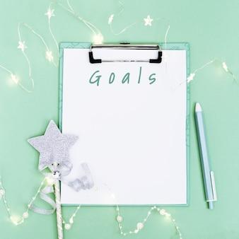 Cahier vierge et stylo pour faire une liste d'objectifs pour la future guirlande lumineuse de décoration de noël