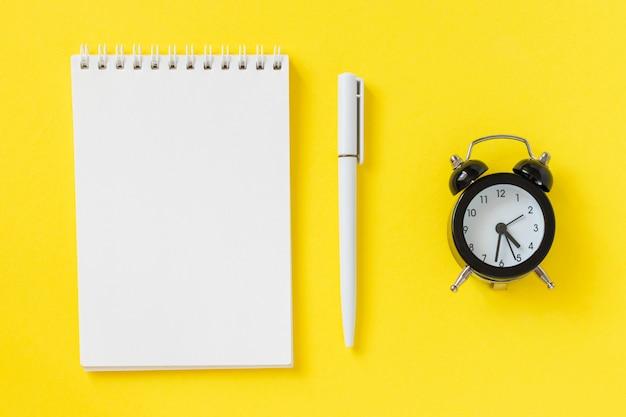 Cahier vierge, stylo et réveil sur fond jaune