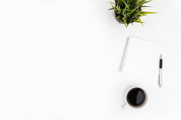 Un cahier vierge avec un stylo se trouve sur la table de bureau blanche avec une tasse de café. vue de dessus avec espace de copie, pose à plat.