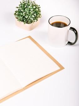 Cahier vierge avec une tasse de café et de fleurs