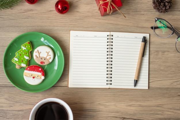 Cahier vierge, tasse à café noire, biscuits de noël et stylo sur table en bois, vue de dessus et espace de copie. noël, bonne année, objectifs, résolution, liste de tâches, concept de stratégie et de plan