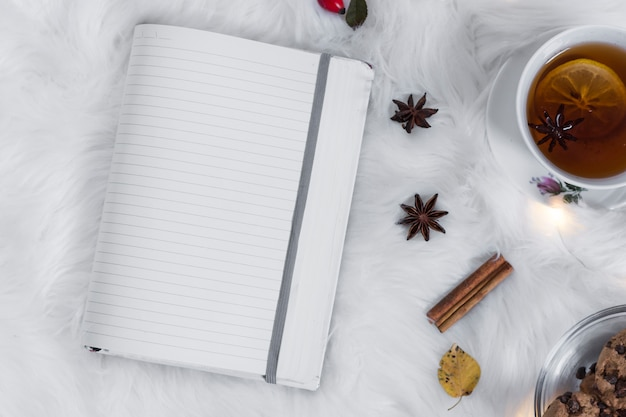 Cahier vierge avec une tasse de thé sur le plaid
