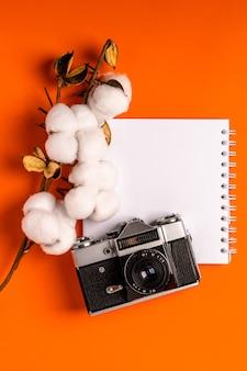 Un cahier vierge vide sur un bureau orange, une branche de coton et un appareil photo vintage