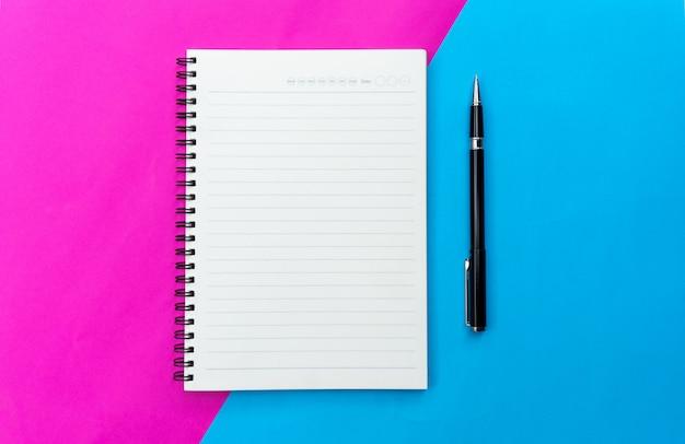 Cahier vierge vue de dessus et un stylo noir pour maquette plate poser sur fond bleu et rose.