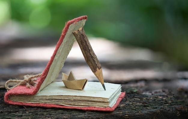 Cahier en vieux papier, crayon en bois et bateau en papier dans la nature.