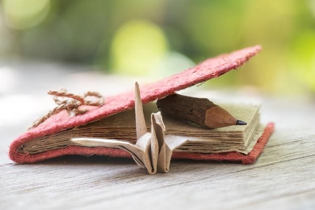 Cahier en vieux papier, crayon en bois et oiseau pater dans la nature.