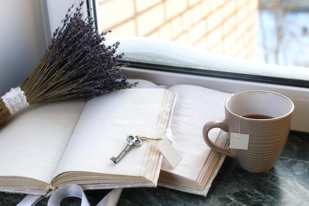 Cahier vintage sur le rebord de la fenêtre en marbre vert ouvert avec des pages blanches et un bouquet de lavande