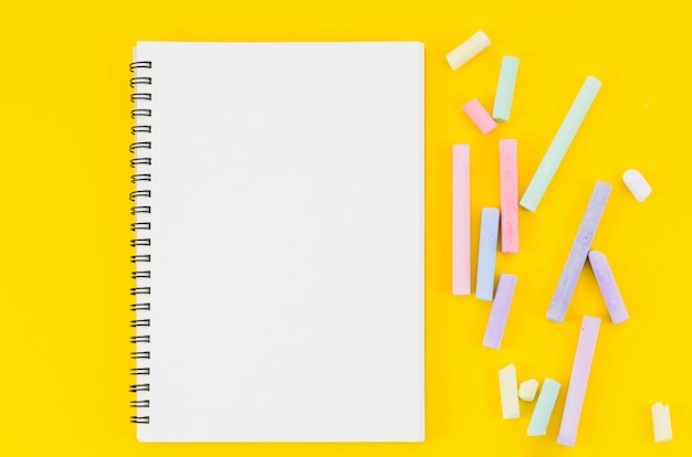 Cahier vue de dessus avec des craies de couleurs pastel