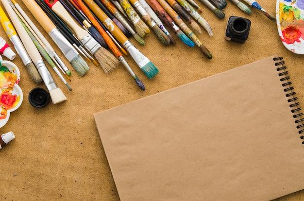 Cahier vue de dessus entouré d'éléments de peinture
