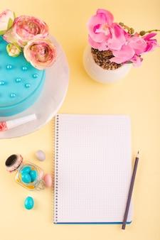 Un cahier de vue de dessus et un gâteau avec des bonbons et des fleurs sur la fête d'anniversaire de bureau jaune