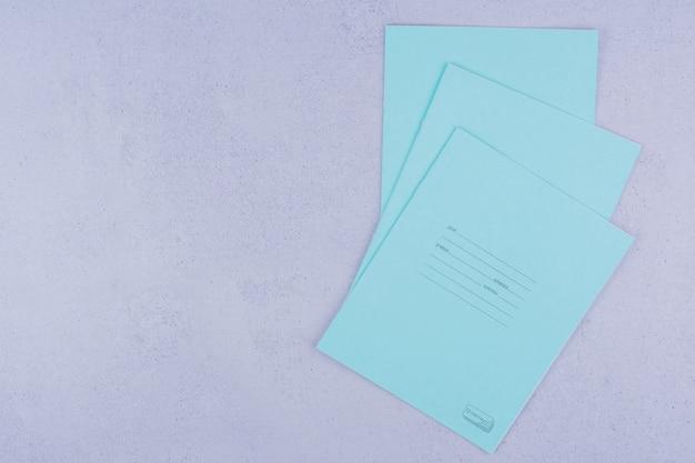 Cahiers bleus isolés sur une surface grise