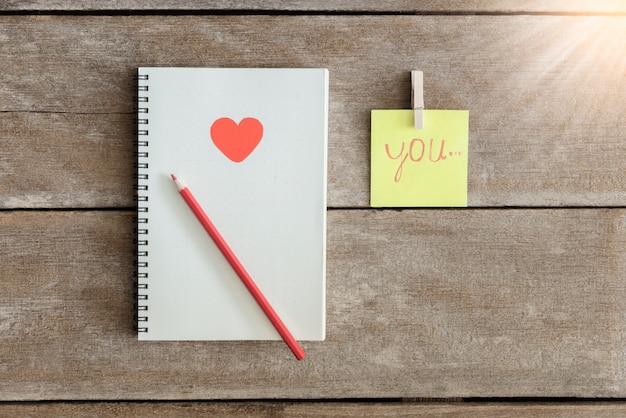 Cahiers, carnets de notes, bloc-notes, crayon arrangés dans le sens je t'aime