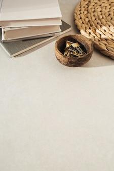 Cahiers, clips dans un bol en bois, support de paille sur béton beige