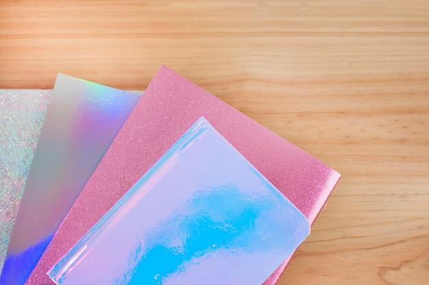 Des cahiers de couleurs irisés avec des paillettes sur un bureau en bois pour la rentrée des classes.