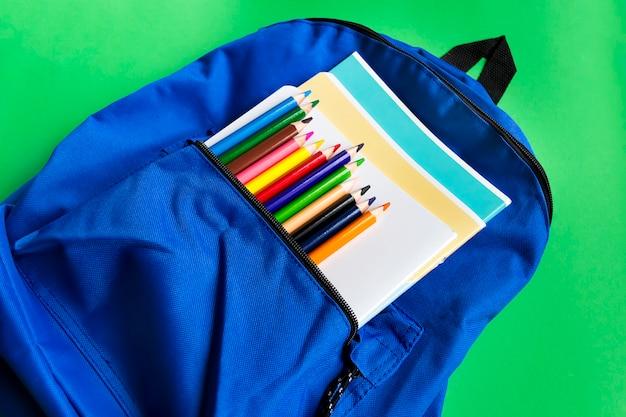 Des cahiers et des crayons multicolores dans un sac à dos sur un fond de papier vert. accessoires d'école. vue de dessus
