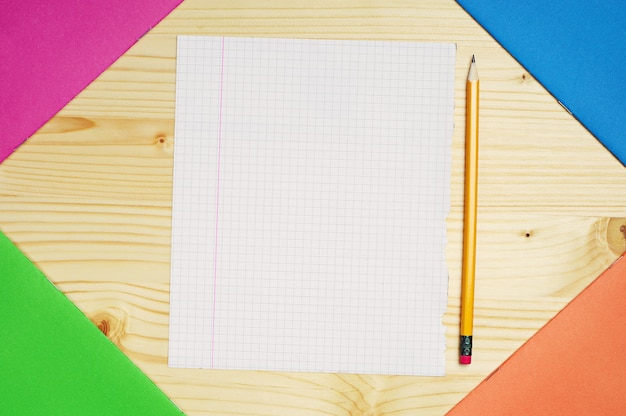 Cahiers d'exercices multicolores et une seule feuille propre sur la table