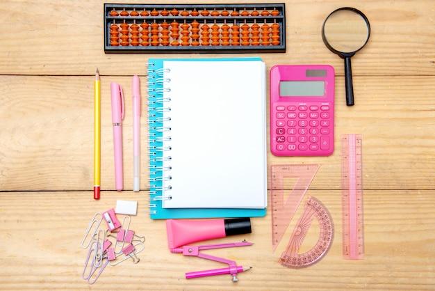 Cahiers avec fournitures scolaires et papeterie sur la table en bois
