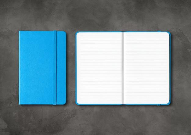 Cahiers lignés fermés et ouverts bleus isolés sur fond de béton foncé