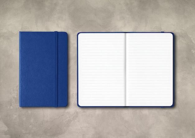 Cahiers lignés ouverts et fermés bleu marine isolés sur fond de béton