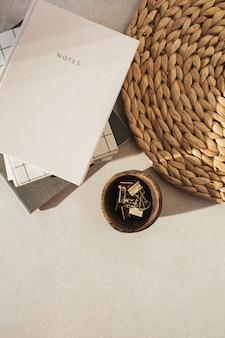 Cahiers à plat, clips dans un bol en bois, support de paille sur béton beige