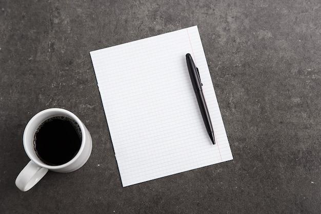 Des cahiers, une tasse de café et des verres sur du marbre gris.
