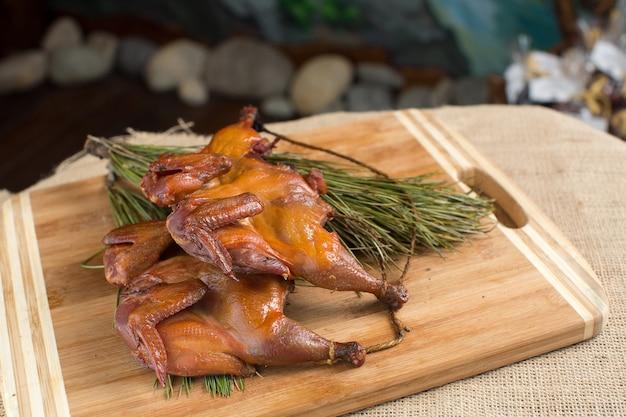 Caille fumée, perdrix, poulets sur un bois