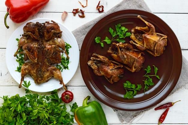 Caille rôtie à la broche. servir sur une assiette en céramique avec des verts. vue de dessus. menu de vacances.