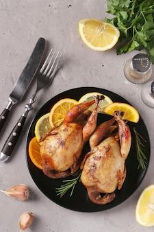 Cailles au four au citron et orange servies sur une assiette foncée sur une surface grise