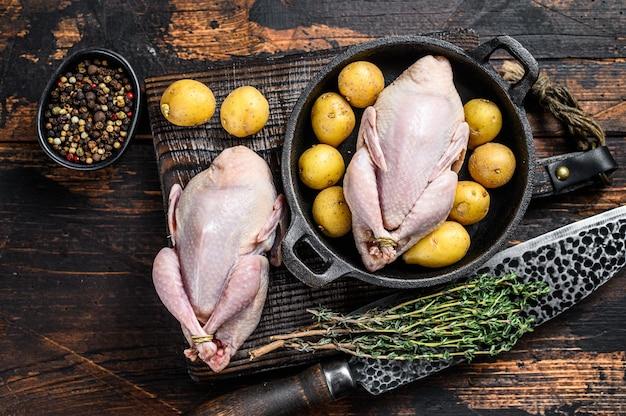 Cailles crues non cuites prêtes à cuire dans une casserole. fond en bois sombre. vue de dessus.
