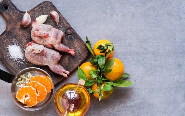 Cailles crues sur la planche à découper prêtes à être cuites aux mandarines