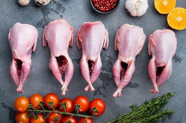 Cailles de viande crue fraîche prêtes pour la cuisson, à plat, sur fond gris