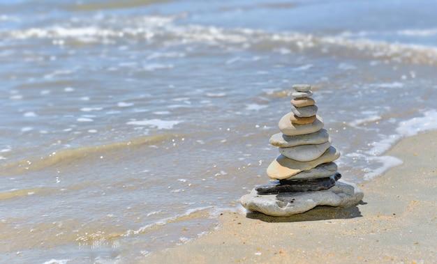 Cailloux empilés au bord de la mer par une journée ensoleillée en été