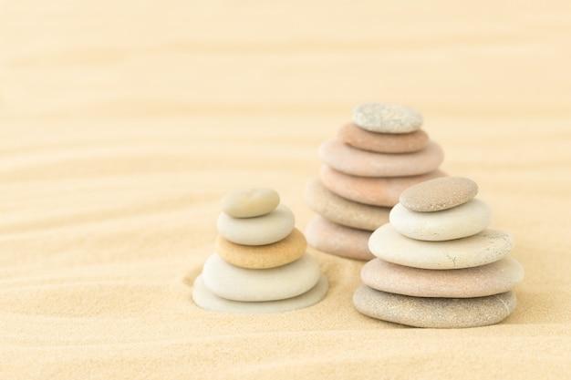Cailloux de mer empilés les uns sur les autres dans le sable un décor d'été pour la détente