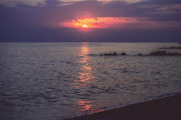 Cailloux sur la plage dans la lumière du coucher du soleil. arrière-plan flou dans les rayons du soleil couchant.