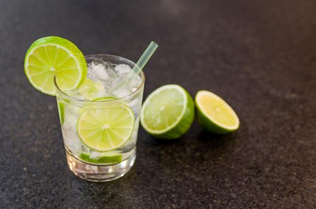 Caipirinha, boisson alcoolisée traditionnelle brésilienne, boisson typique à base de sucre, citron, canne distillée (cachaca) et glace. ingrédients et boisson sur une surface de granit noir.