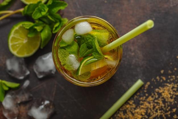 Caïpirinha traditionnelle brésilienne avec citron vert, sucre et menthe. fond sombre, vue de dessus, espace de copie.