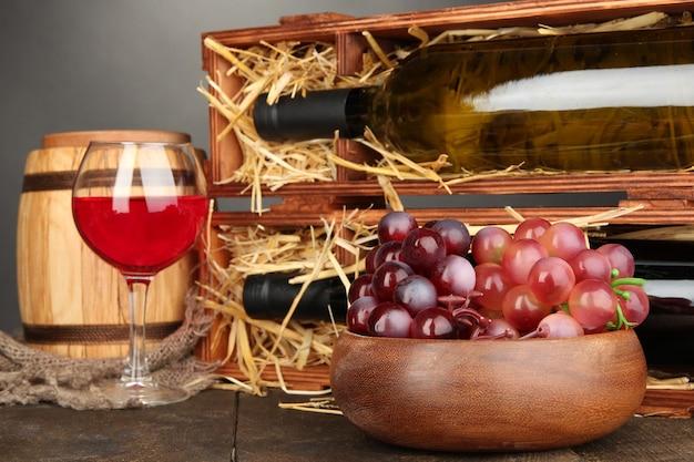 Caisse en bois avec bouteilles de vin, baril, verre à vin et raisin sur table en bois sur surface grise