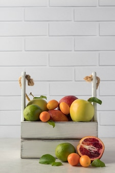 Caisse en bois avec différents fruits exotiques sur table, espace pour votre texte