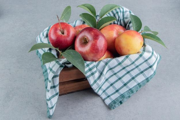 Une caisse couverte de serviettes et un paquet de pommes sur du marbre